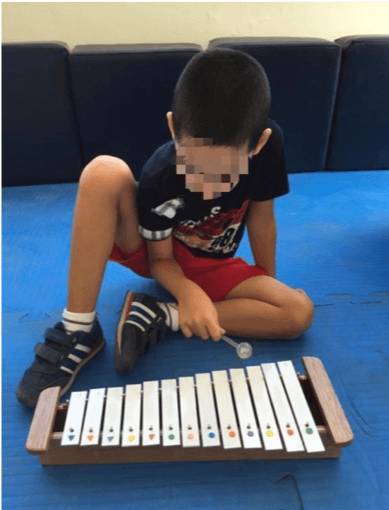 kid with special needs playing music instrument
