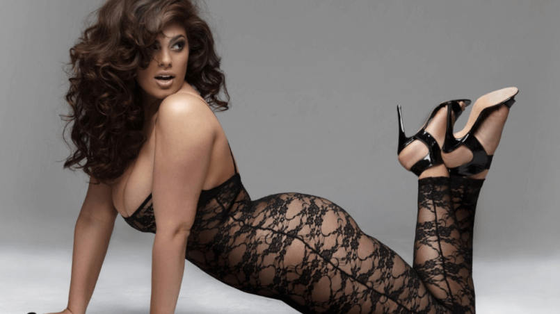 Ashley Graham plus size model posing wearing black dentelle dress with high heels